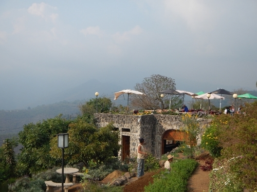 The patio of a restaurant that was             on a mountain overlooking Antigua