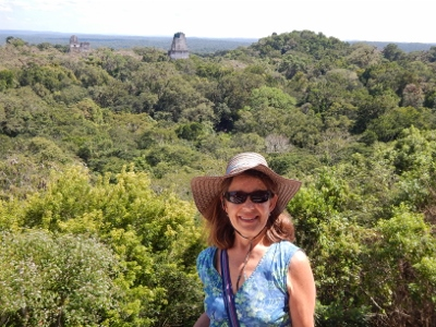 Behind Kathy is the view from our vantage point on Monument         four in Tikal National Park